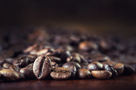 Roasted coffee beans spilled freely on a wooden table.Coffee time ** Note: Shallow depth of field